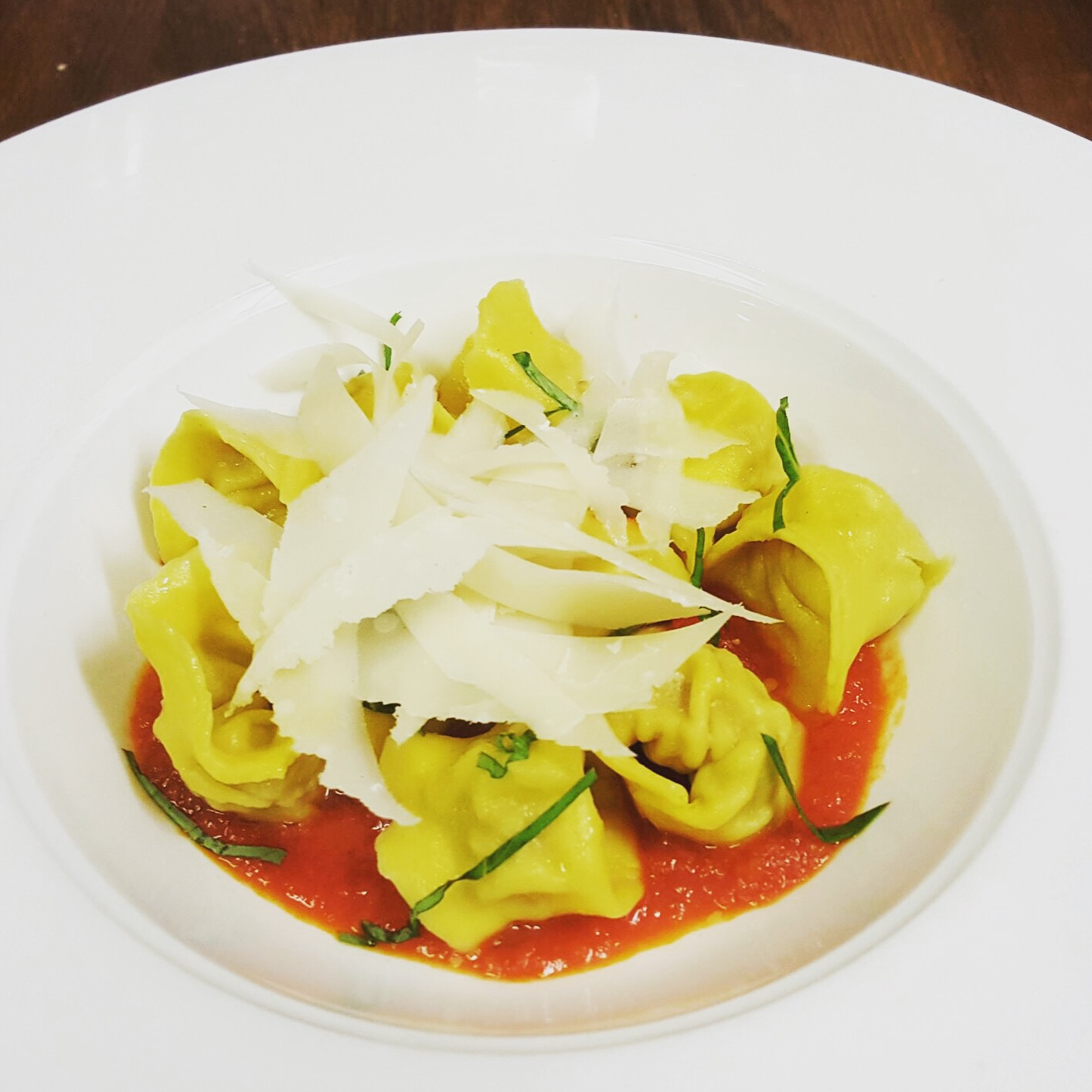 Homemade meat tortellini with tomato sauce and parmesan shavings