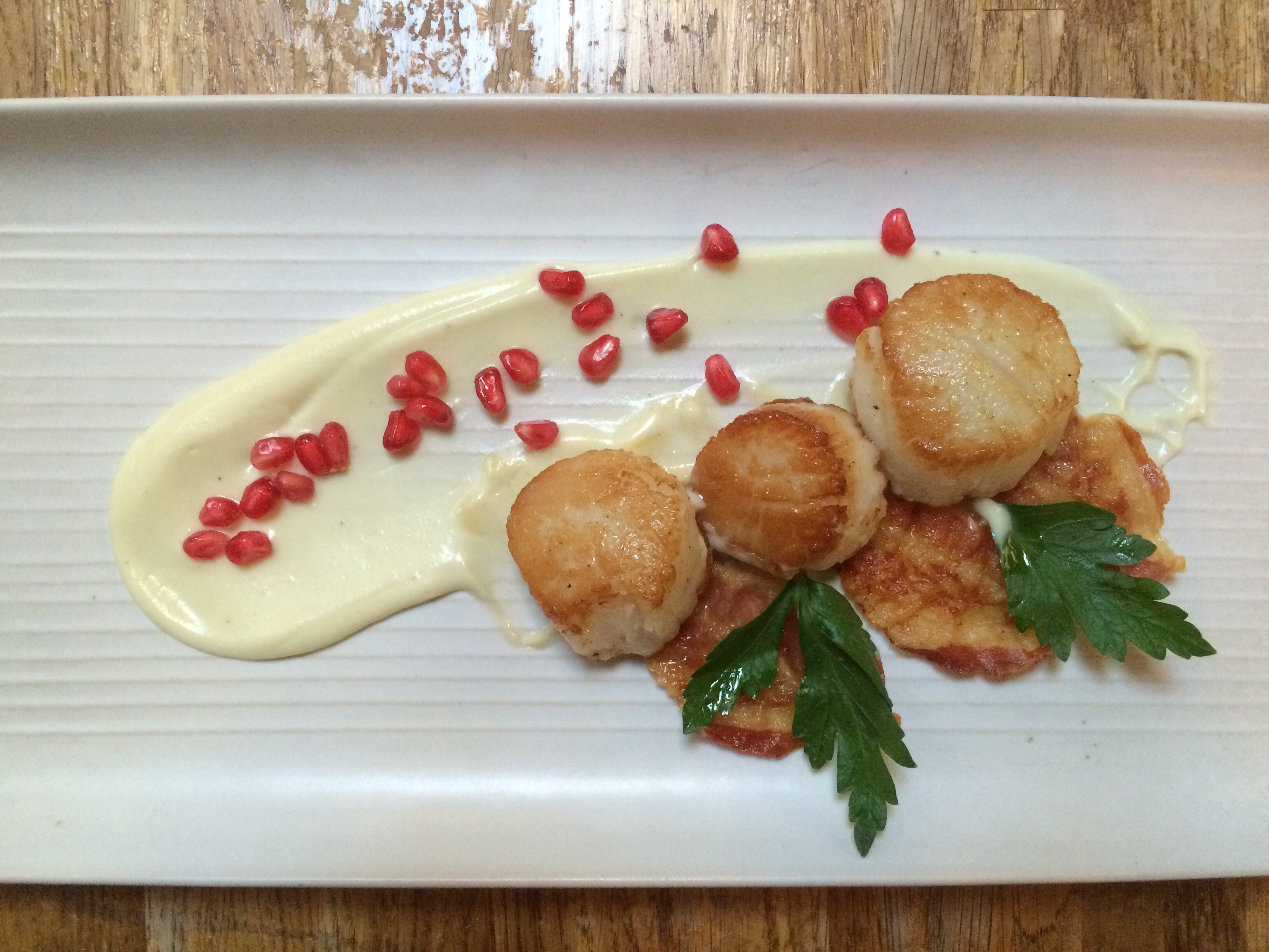 Scallops with cauliflower puree, pomegranate and crispy pancetta